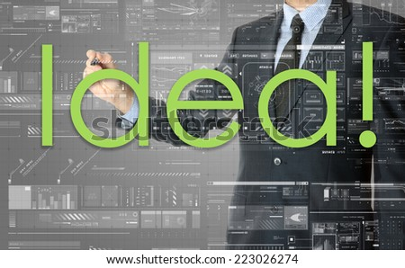 the businessman is writing Idea ! on the transparent board with some diagrams and infocharts with the dark elegant background - stock photo