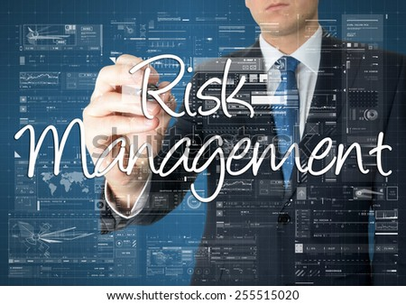 the businessman is writing Risk Management on the transparent board with some diagrams and infocharts - stock photo