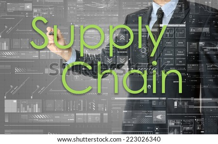 the businessman is writing Supply Chain on the transparent board with some diagrams and infocharts with the dark elegant background - stock photo