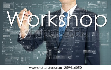 the businessman is writing Workshop on the transparent board with some diagrams and infocharts - stock photo