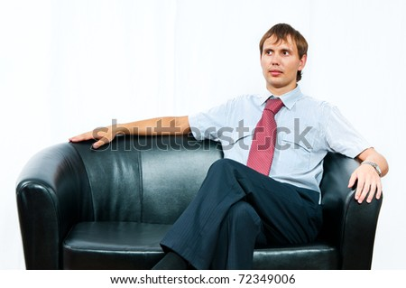 The businessman sits on a sofa on a white background