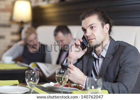 The businessman sitting at a table in cafe, using the laptop, speaks by phone.