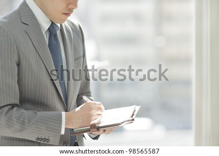 The businessman who fills out a notebook