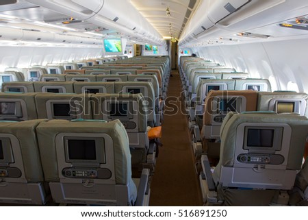 The cabin of passenger aircraft. Economy class. Armchairs with screens of onboard entertainment system.