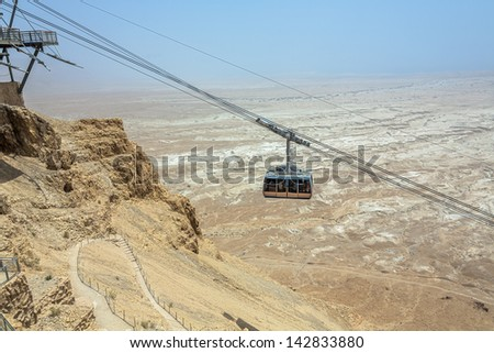 The cable car transporting passengers in ancient fortress Masada - Israel - stock photo