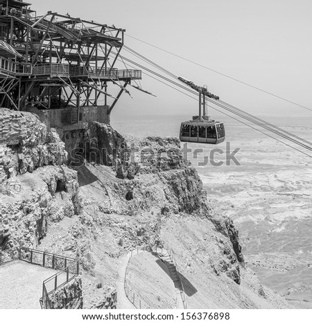 The cable car transporting passengers in ancient fortress Masada - Israel (black and white) - stock photo