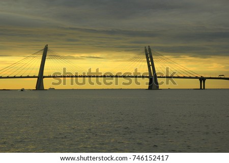 The cable-stayed bridge across the Neva river against the background of the sunset