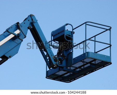 The Cage at the Top of a Blue Cherry Picker Lift. - stock photo