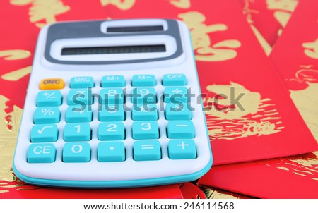 The calculator is placed on amount of the Chinese New Year red envelopes. - stock photo