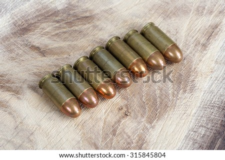 The .45 caliber cartridge on wooden background - stock photo
