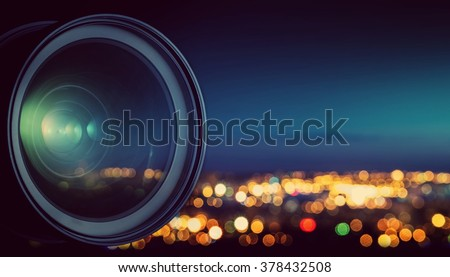 The camera lens on the background blurry city lights. - stock photo