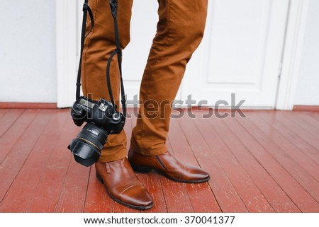 The camera on the strap, leg, outdoors, walk