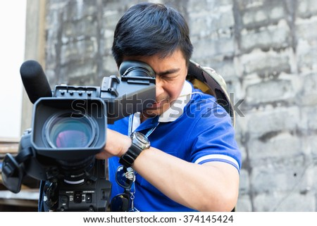 The cameraman filming outdoor event - stock photo