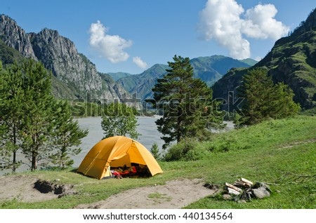 The Camping Tent near mountain river in the summer - stock photo