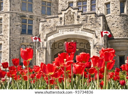 The Canadian Parliament Confederation Building with flags on Wellington Street in Ottawa during Spring with red tulips.