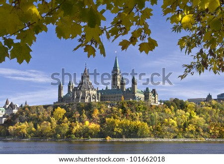 The canadian Parliament framed with Autumn leaves across the Ottawa river. - stock photo