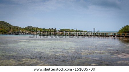 The canal between Santa Catalina and Providencia with the Lovers Bridge in the distance - stock photo