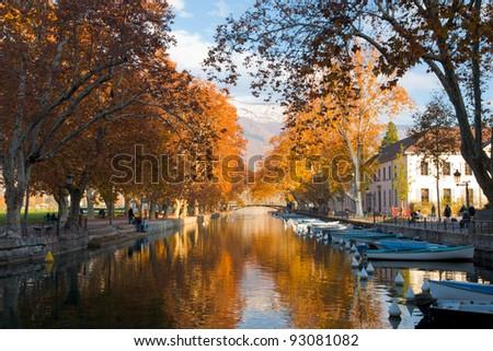 The canal in Annecy, France ringed by the beautifully colored autumn leaves - stock photo