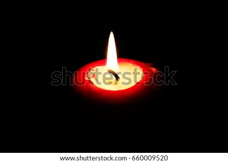 The candle flame on the black background