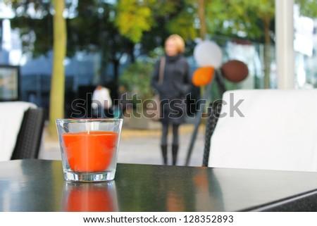 The candle on the table in the autumn cafe