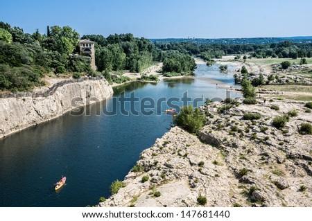 The canyon of Gardon river under the Bridge of Pont du Gard, near Nimes, France - stock photo