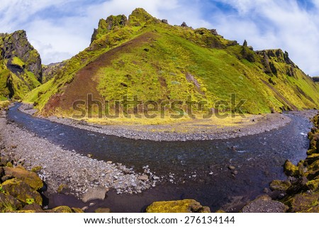 The canyon Pakgil is located among fantastic rocks. On bottom of canyon  fast shallow stream flows. The summer blossoming Iceland. The photo was taken Fisheye lens - stock photo