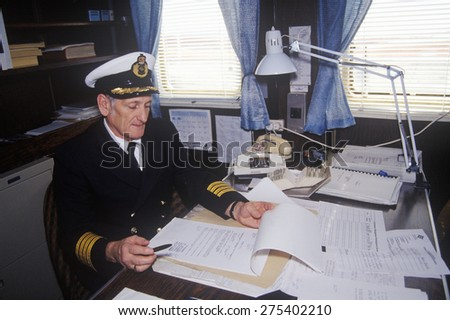 The captain of the ferry Bluenose doing paperwork at his desk, Maine