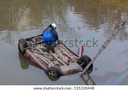 The car fell into the water and capsized. Rescuer attaches the rope. - stock photo