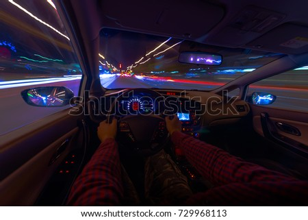 The car's movement at night with a kind of speed from the inside, a brilliant road with lights with a car at high speed. Car dashboard
