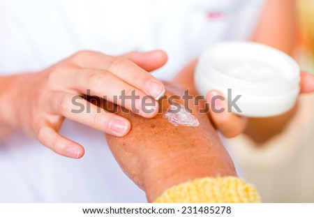 The carer rubbing the elderly woman's hand  with cream  - stock photo