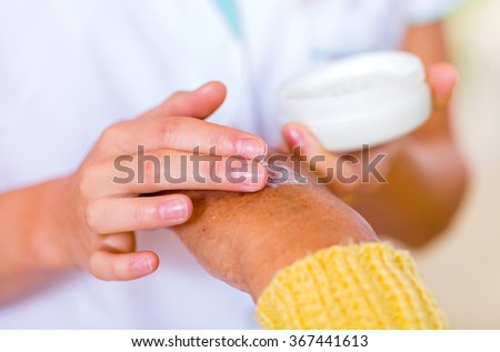 The carer rubbing the elderly woman's hand  with cream
