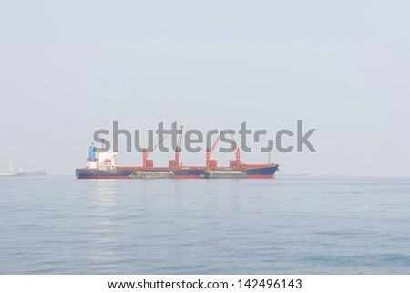 The cargo ship in the Gulf of Thailand with the sea fog