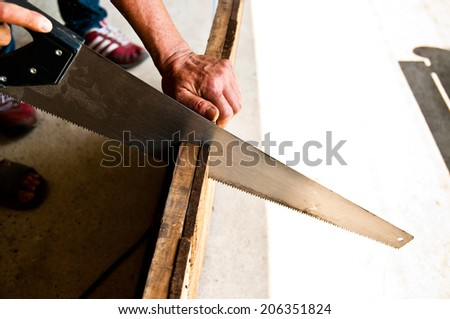 The Carpenter Sawing Down Wood, Cutting, Making Furniture by Hand / Concept and Idea of Workshop Carpentry Business and Carpenter Wood Work. Real Still Life Style. - stock photo