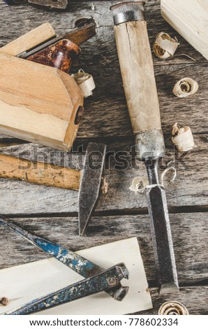 The carpenter tools on a wooden bench, a planer, chisel, hammer, tongs, top view
