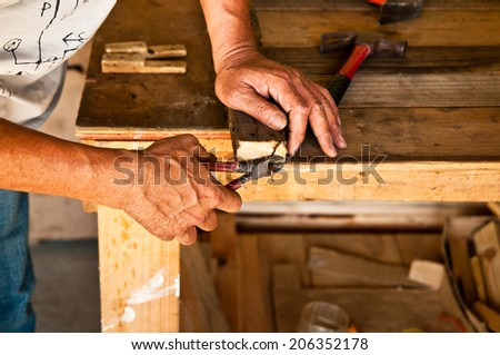 The Carpenter Use Pliers or Pincer to Get a Nail from Wood, Making a Furniture / Concept and Idea of Carpentry Business and Carpenter Wood Work. - stock photo