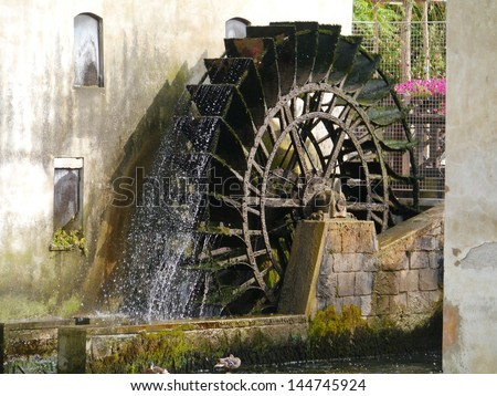 The carriage wheel of a water mill in Portogruaro a town on the river Lemene in the Province Venice in Veneto in Italy - stock photo