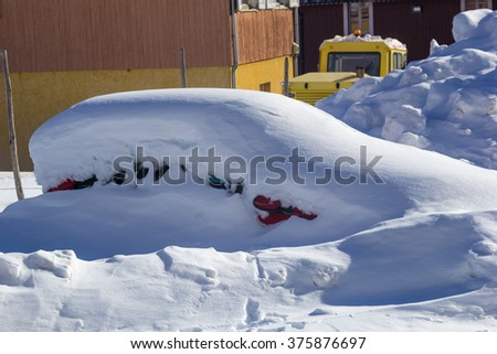 The cars on the parking under snow.