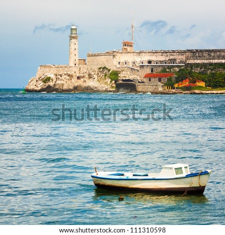 The Castle of El Morro, a worldwide known  landmark of Havana with a small fishing boat on the foreground - stock photo