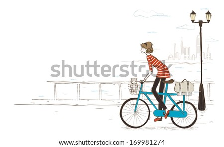The cat is riding in the ladies bicycle basket. - stock photo