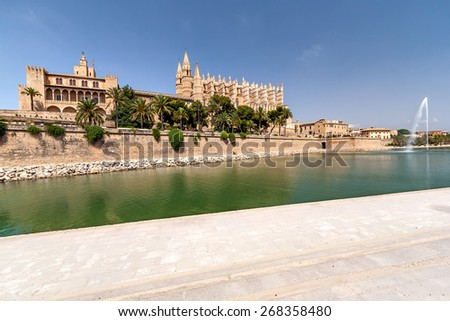The Cathedral and the fountain in the center of Palma de Mallorca. Panorama of the Cathedral and the fountain in Palma de Mallorca in the summer sunny day. Water, palm trees, cloudless sky. - stock photo