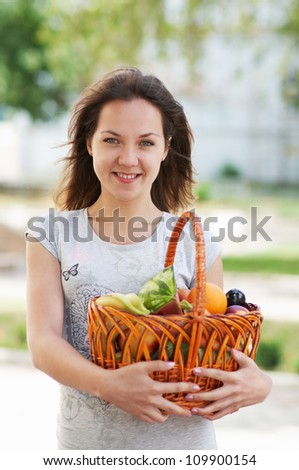 The caucasian girl with basket of food in the street