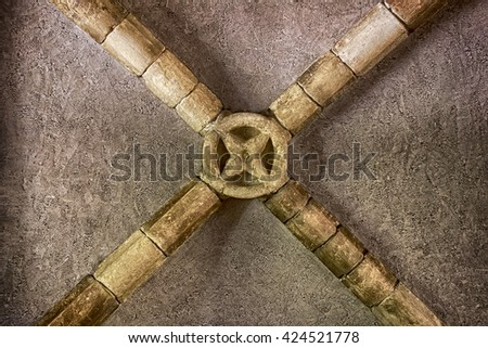 The center of a vaulted ceiling shows the stone beams centered with a circular ornament. - stock photo