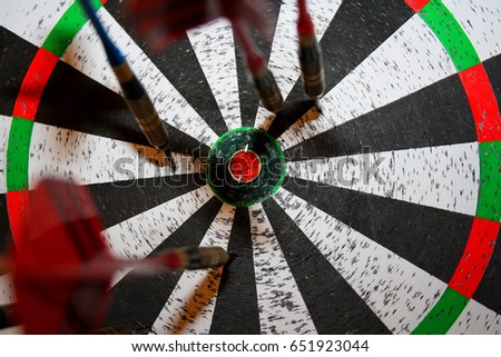 The center of the target dartboard with Darts sticking with feathers