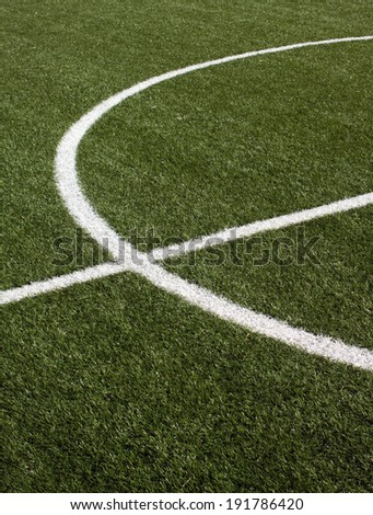 The center part of a soccer field with green synthetic grass and white lines on it vertical view closeup