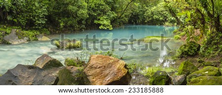 The cerulean blue waters of the 'Blue Lagoon' on the Rio Celeste in Volcan Tenorio National Park, Costa Rica. - stock photo