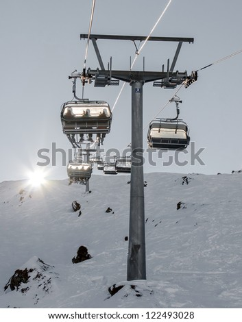 The chair lift and rope tow systems of Kaprun region of the back light, Austria - stock photo