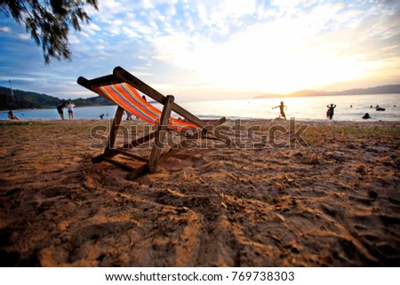 The chair on the beach in the evening. And there are people playing the water. Relax