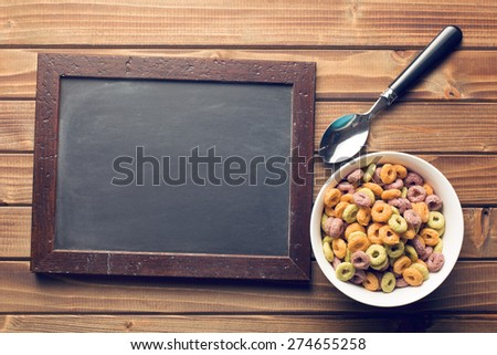 the chalkboard and colorful cereal rings in spoon - stock photo
