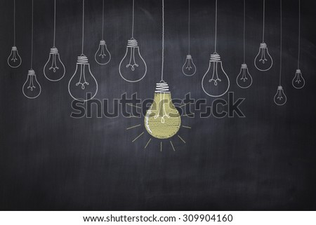 The chalkboard drawing shows light bulbs in a row with a big one glowing. - stock photo