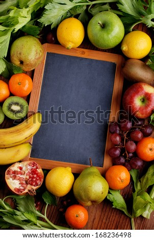 the chalkboard with fresh fruits around - stock photo